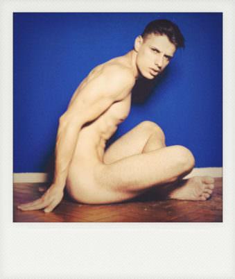 Polaroid eines nackten, sitzenden jungen Mannes vor blauer Wand.