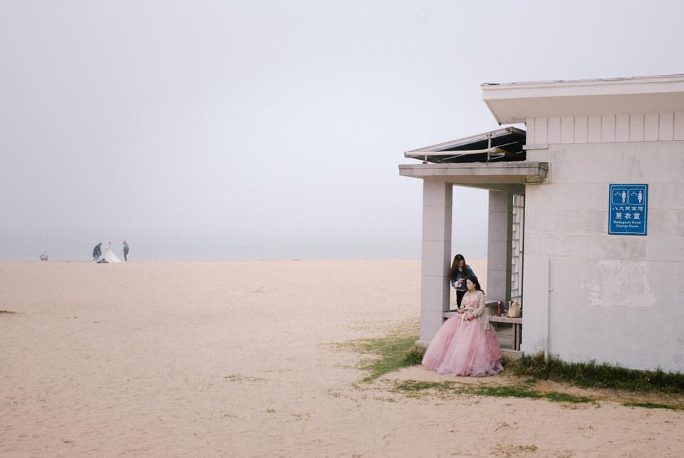 Eine Braut sitzt am Strand