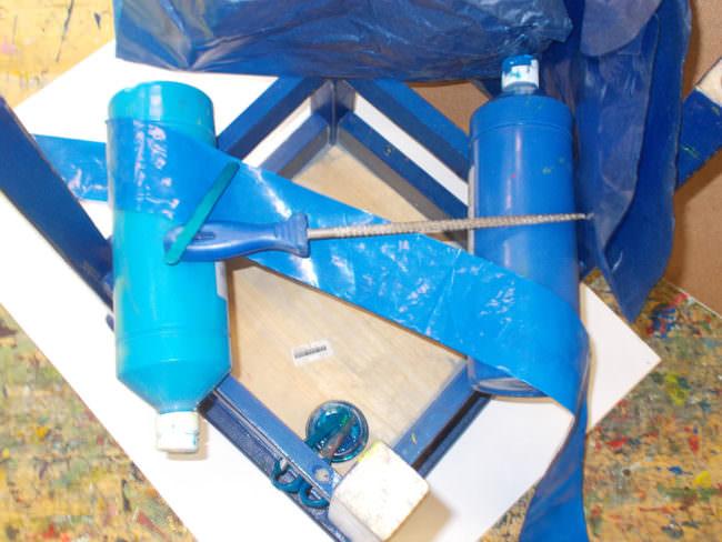 Ansammlung blauer Gegenstände, Plastikband, Pinsel, Stuhlunterseite und Farbtuben.