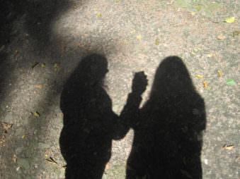 Schatten auf Waldboden von 2 Frauen.