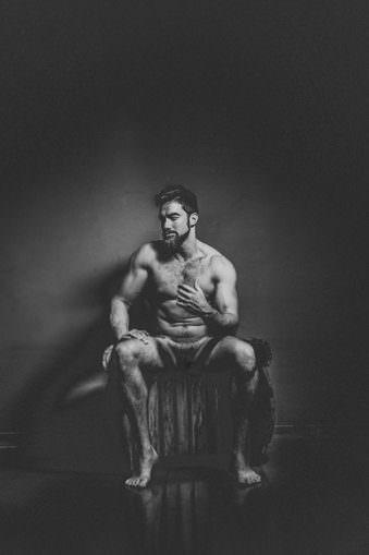 Nackter Mann sitzt auf Hocker und gestikuliert.