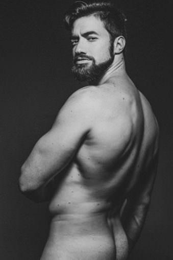 Mann mit Bart und freiem Oberkörper der von einem abgewandt ist Blickt keck über die Schulter