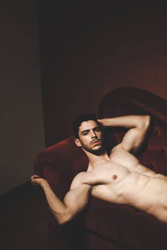 Mann mit nacktem Oberkörper liegt mit dem Rücken auf rotem Sofa und blickt einen an.