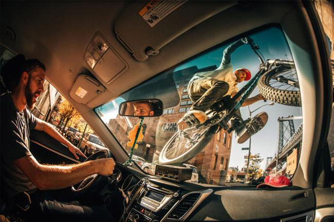 Aussicht aus einem Auto auf dessen Front ein BMX-Fahrer fährt
