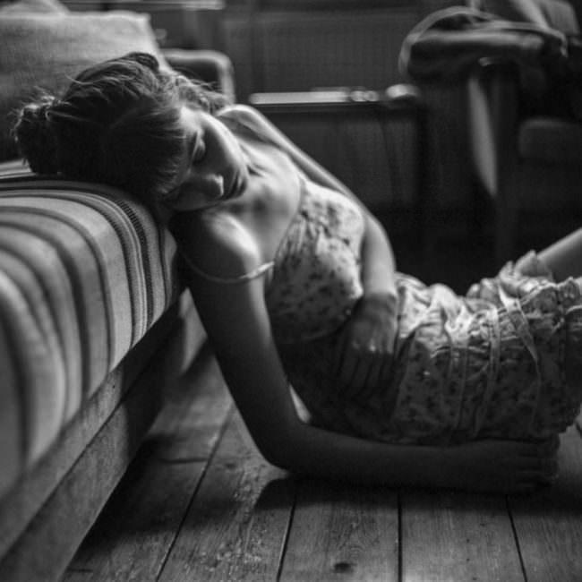 Eine Frau sitzt auf dem Boden mit dem Kopf nach hinten aufs Sofa gelehnt