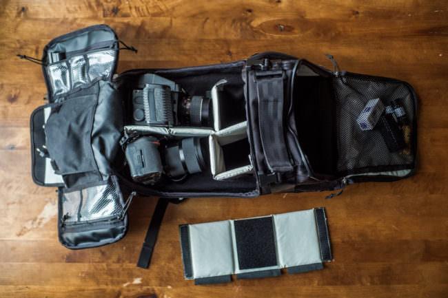 Ein geöffneter Rucksack, in dem sich zwei Kameras befinden