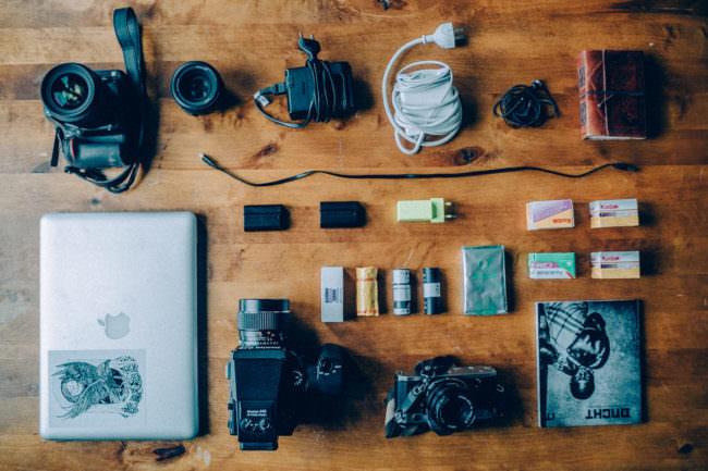 Auf einem Tisch liegen Kameras und Zubehör ausgebreitet