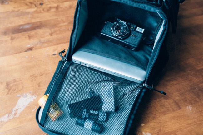 Eine Kamera und Filme liegen in einem Rucksack