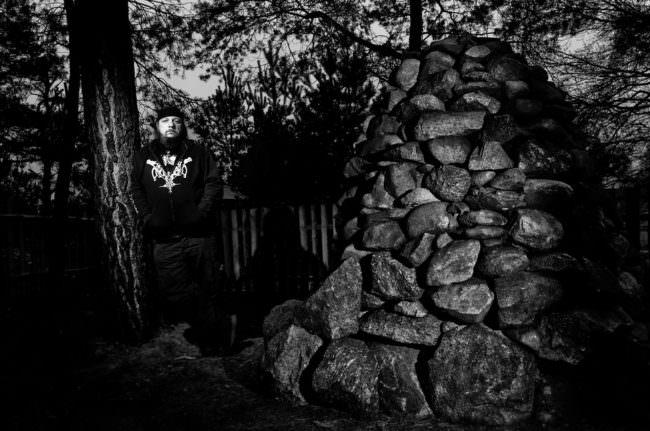 Großer aufgetürmter Steinhaufen neben dem ein Mann mit Tribalpullover steht.