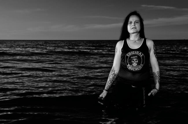 Frau stehend vor Meereshintergrund in schwarzweiß