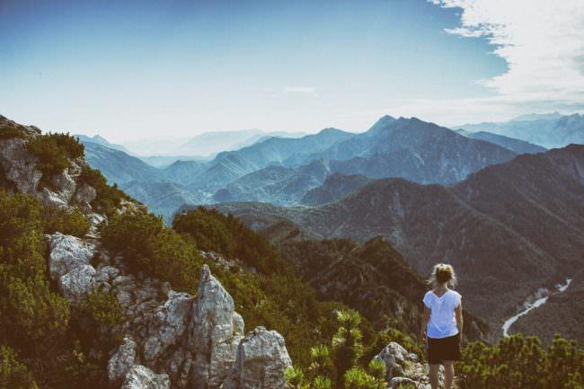 Mädchen steht auf einem Gipfel