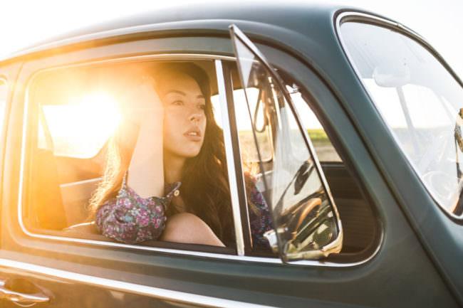Frau im Auto im Gegenlicht