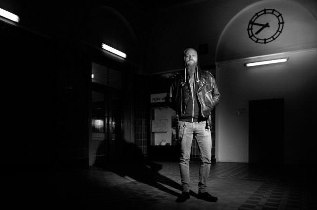 Junger Mann in Lederjacke und Jeans vor Gebäude