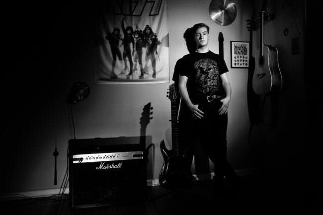 Junger Mann stehend neben Amp und Gitarre lehnt an Wand mit Bandposter.