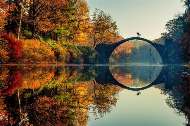 Ein Fahrradfahrer auf einer märchenhaften Brücke im Herbst