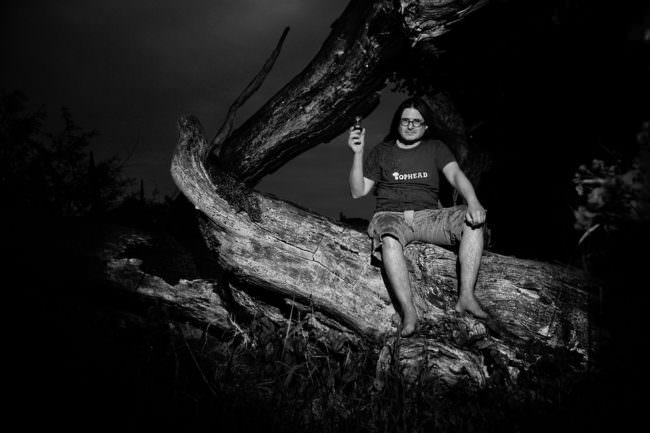 Mann sitzt auf abgestorbenem Baumstamm