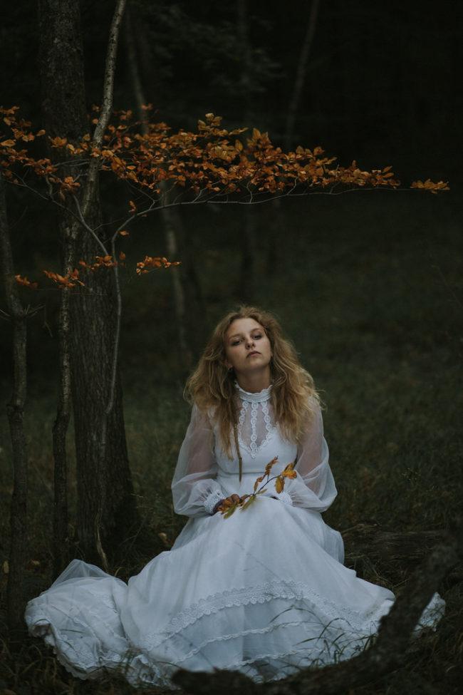 Mädchen in weißem Kleid unter einem Herbstbaum