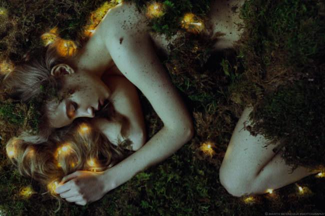 Eine Frau liegt im Moos mit Lichtern