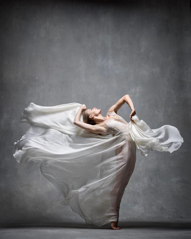 Eine Frau tanzt mit fließenden weißen Kleidern
