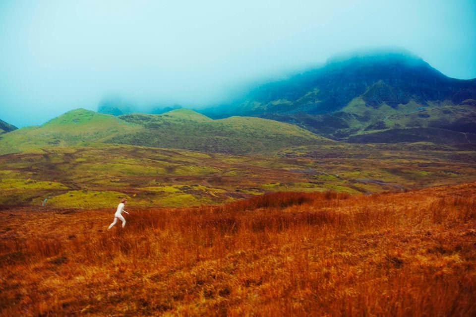 Ein Mann rennt nackt zwischen roten Gräsern
