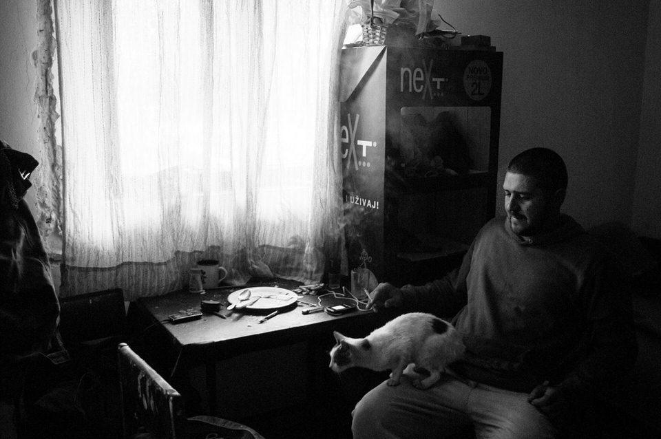 Ein Mann sitzt an einem Fenster mit Katze auf dem Schoß
