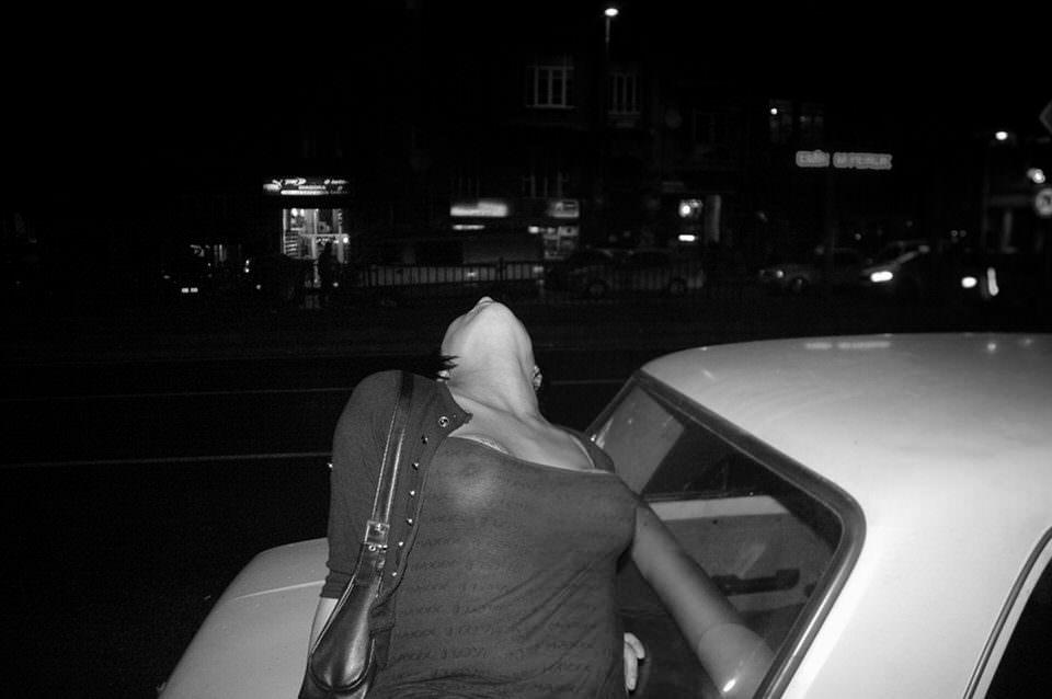 Frau lehnt sich auf ein Auto