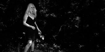 Frau in kurzem schwarzen Kleid vor dunklem Waldhintergrund.