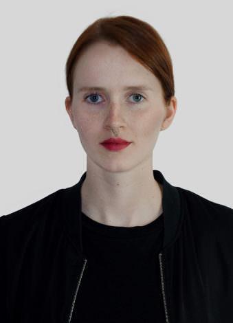 Eine Frau mit roten Haaren und Zopf.