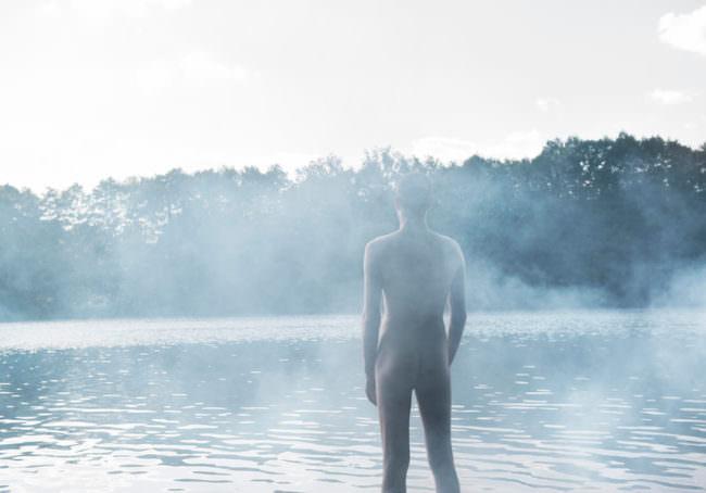 Ein nackter Mann vor einem See