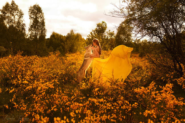 Eine Frau im gelben Kleid mit einem Hund