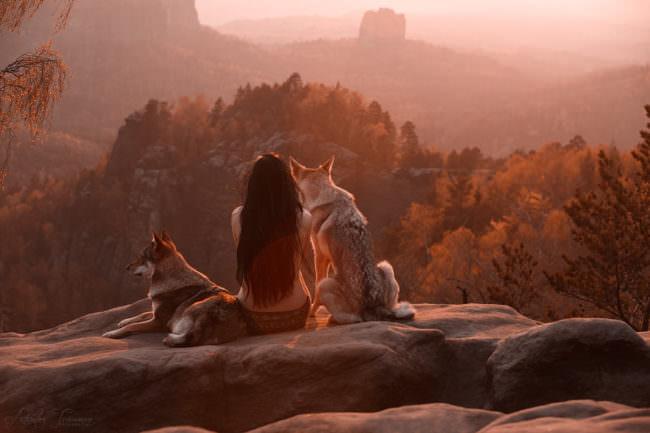 Zwei Hunde mit einer Frau auf einem Felsen im Sonnenuntergang