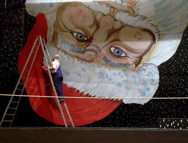 Wandbild vom Weihnachtsmann auf dem Kopf, davon ein Mann auf einer Leiter in Blaumann.