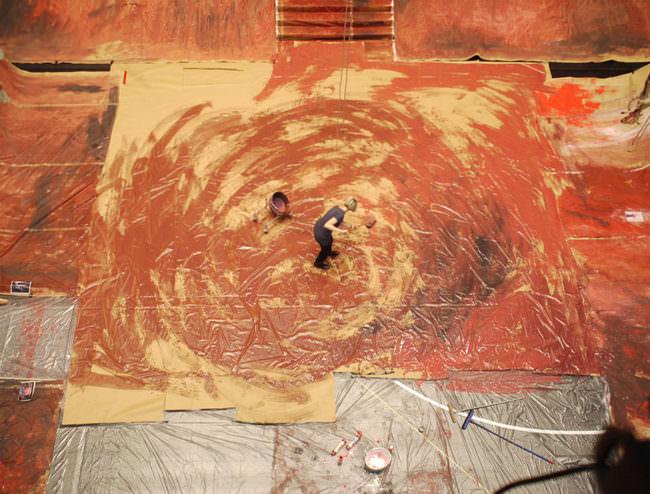 Person streicht einen Fußboden rötlich an, sodass es beinahe ein Kreisbild ergibt.