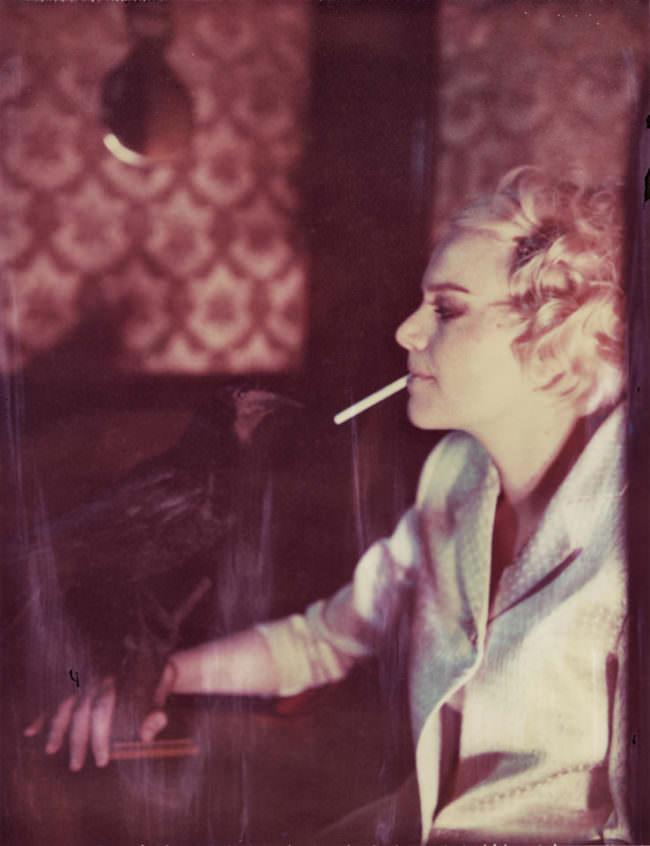Portrait einer Frau mit Zigarette und ausgetopften Raben in der Hand
