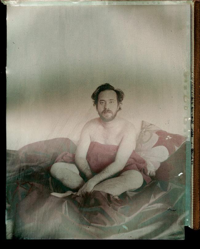 Aktaufnahme eines Mannes auf einem Bett, der sich ein Kissen vor den Körper hält