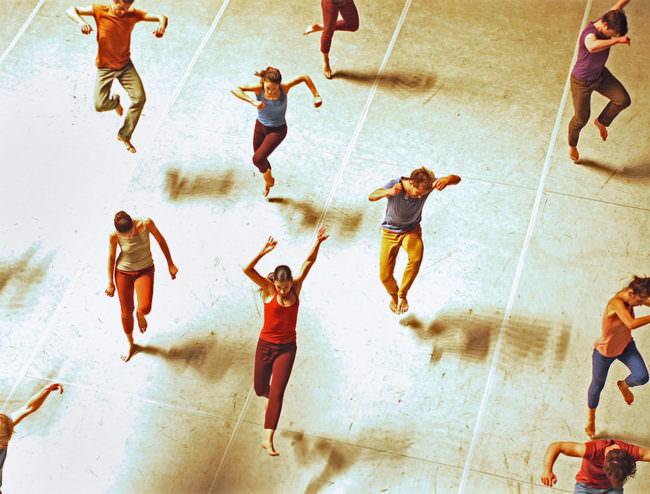 Tanzende und springende Personen in bunten Kleidungsstücken von oben dargestellt.