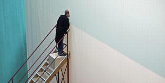 Mann steht auf Treppe und schaut durch ein Loch in einer Wand.