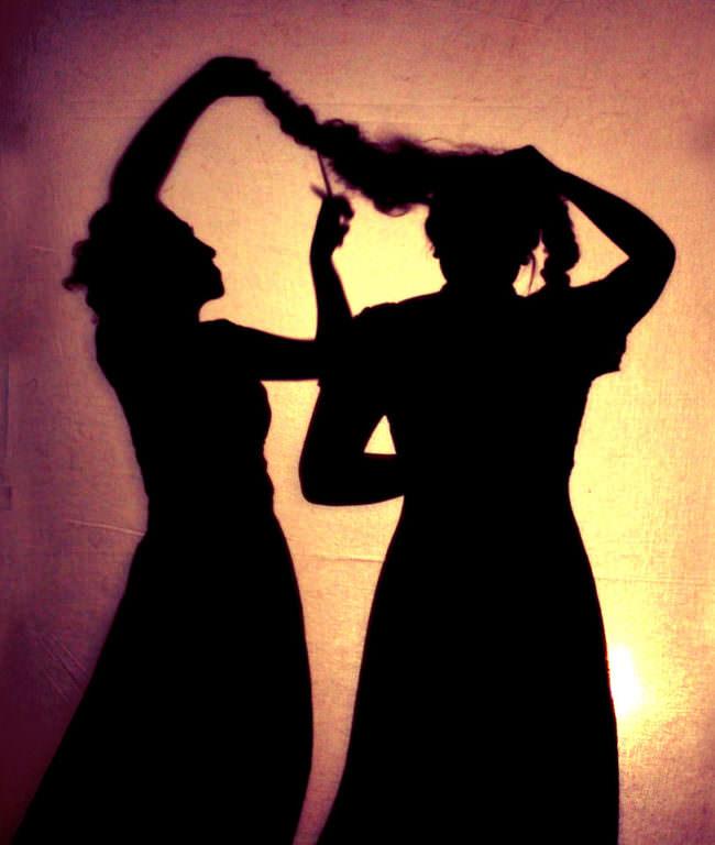 Zwei Silhouette von Frauen, die sich Haare schneiden