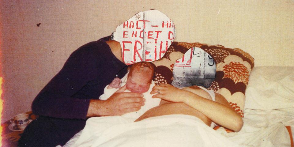 Ansicht einer alten Fotografie von einem Paar mit Baby auf einem Bett mit überklebten Köpfen.