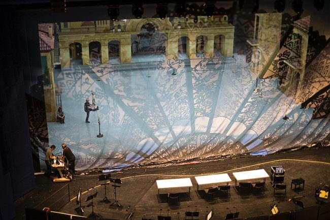 Schattenspiel auf eine Bühnenkulisse mit Architektur im Hintergrund.