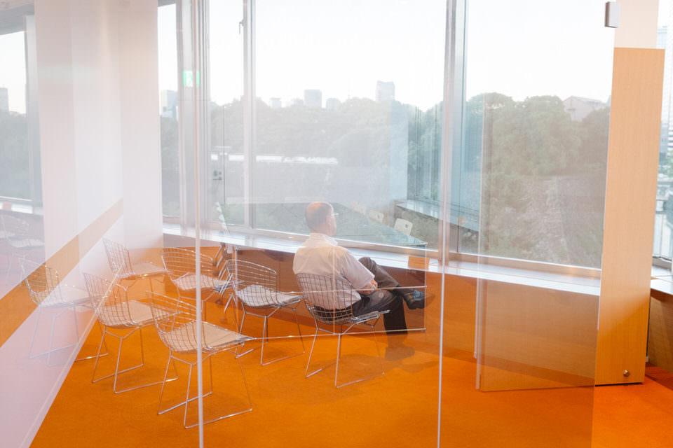 Ein Mann auf einem Glasstuhl sieht aus einem Fenster