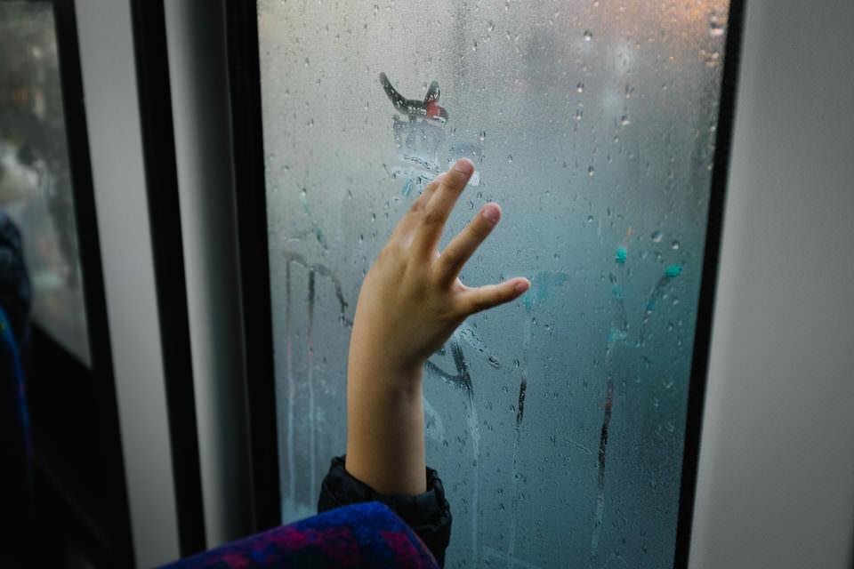 Eine Kinderhand malt an beschlagene Fenster