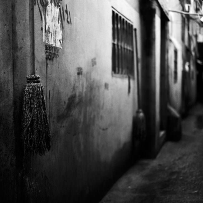 Ein Besen hängt in einer Gasse an einer heruntergekommenen Wand
