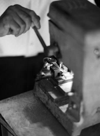 Nahaufnahme eines Schlüssels der an einer mechanischen Maschine gefertigt wird