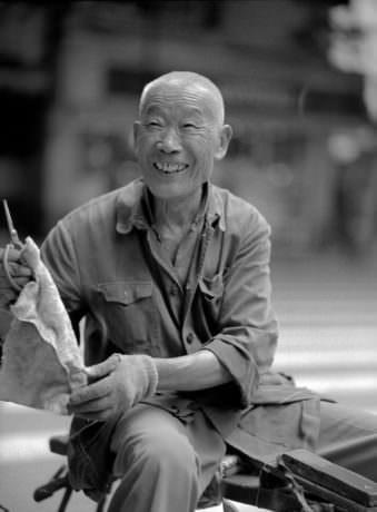 Asiatischer Mann mit Handschuhen hält ein Stück in der Hand und lächelt