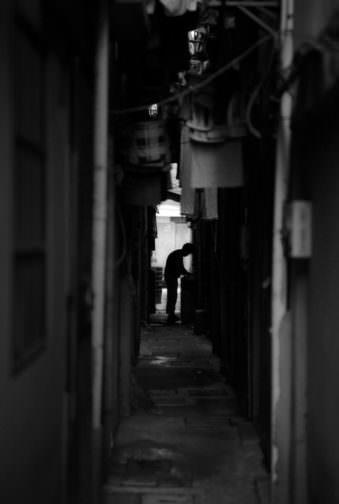 Enge Straße mit aufgehängter Wäsche und der Silhouette eines Mannes