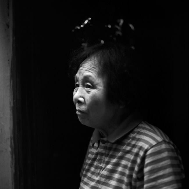 Portait einer asiatischen Frau vor dunklem Hintergrund