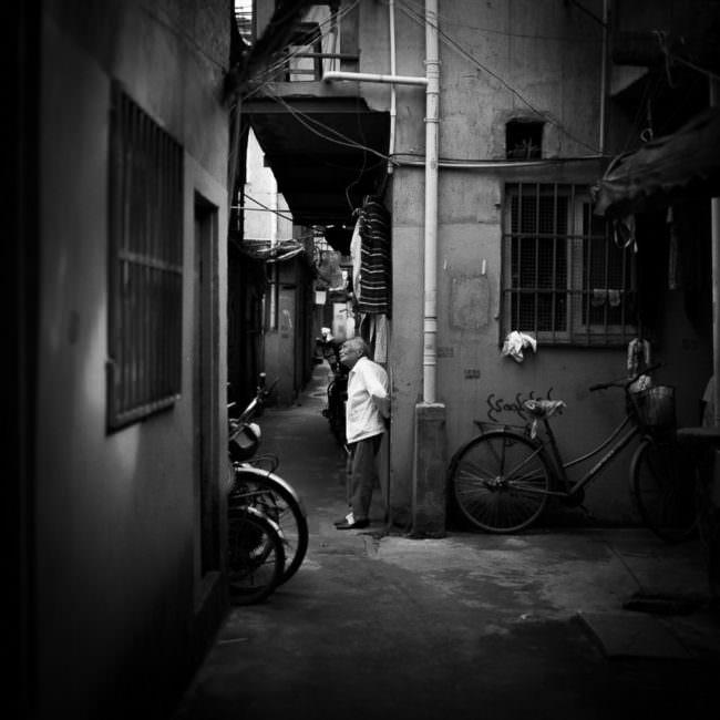 Mann in enger Straße mit geparkten Fahrrädern lehnt an einer Wand und sieht nach oben