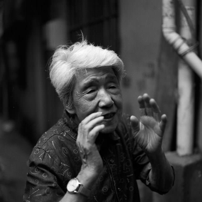 Asiatische Frau mit weißen Haaren gestikuliert mit den Händen