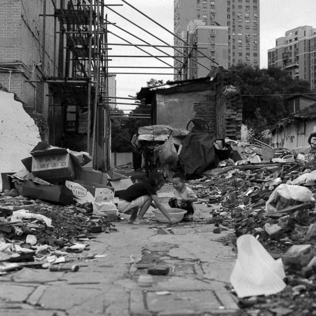 Asiatische Kinder spielen im Bauschutt vor Hochhäusern